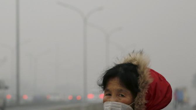 A woman wearing a protective mask makes her way on an extremely polluted day as hazardous, choking smog continues to blanket Beijing