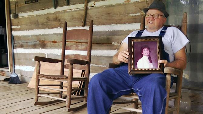 In this Friday, Aug. 10, 2012 photo, James Davis holds a photo of his late wife, Patsy Davis, on the porch of their home in Stevenson, Ala. Davis buried his wife in their front yard, and the city filed suit to force him to remove the remains. Davis is fighting a court order requiring him to disinter the body. (AP Photo/Jay Reeves)