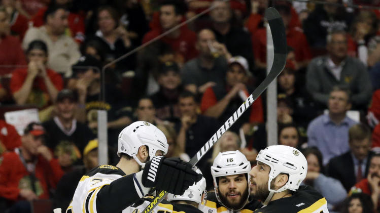Boston Bruins left wing Milan Lucic, right, celebrates with his teammates including Dennis Seidenberg (44) after scoring a goal against the Chicago Blackhawks during the first period of Game 1 in their NHL Stanley Cup Final hockey series, Wednesday, June 12, 2013, in Chicago. (AP Photo/Nam Y. Huh)