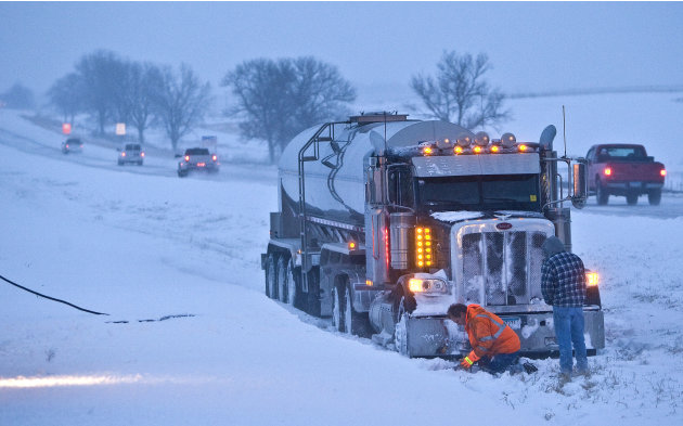 A towing crew from Moody's of Rochester, Minn. hooks up a tanker trailer truck that lost control and landed in the median of U.S. 52 North near Oronocco, Minn. Thursday, Dec. 20, 2012.  The first majo
