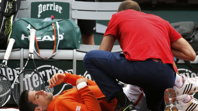 Novak Djokovic of Serbia gets medical assistance during the men's singles match against Gilles Muller of Luxembourg at the French Open tennis tournament at the Roland Garros stadium in Paris