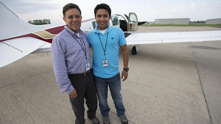 In this Thursday, June 19, 2014 photo, Babar Suleman and son Haris Suleman, 17, stand next to their plane at an airport in Greenwood, Ind. before taking off for an around-the-world flight. On Wednesday, July 23, 2014, a single-engine plane with two aboard crashed in waters off American Samoa, with a registration number matching the plane flown by the Indiana teen attempting to fly around the world in 30 days. (AP Photo/The Indianapolis Star, Robert Scheer)