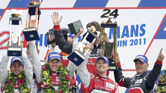 The Audi R18 TDI No2 drivers from left, Benoit Treluyer of France, Andre Lotterer of Germany and Marcel Fassler of Switzerland,  andAudi Motorsport Chief Dr Wolfgang Ullrich react with their trophy on the podium, after the 79th 24-hour Le Mans endurance race, in Le Mans, western France, Sunday, June 12, 2011. (AP Photo/Vincent Michel)