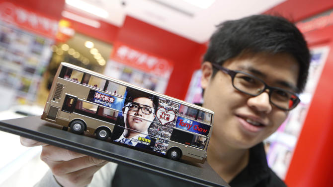 In this Dec. 9, 2013 photo, English grammar tutor Tony Chow, shows his advertising plan with a model of a double decker bus having his face plastered on the sides as to raise his profile further in Hong Kong. The 30-year-old teaches English grammar to thousands of secondary school pupils, who attend his after-school lessons or watch video replays of them at Modern Education's 14 branches. Chow is a celebrity tutor in Hong Kong, where there's big money to be made offering extracurricular lessons to parents desperately seeking an edge for their children preparing for the city's intense public entrance exam for university. (AP Photo/Kin Cheung)