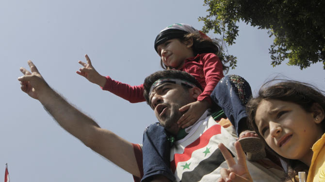 """A Syrian family shouts anti- Syrian President Bashar Asssad slogans as they wear Syrian independence flags during anti-Syrian regime protest outside the Arab League headquarters in Cairo, Egypt, Sunday, July 3, 2011, to support the Syrian demonstrators who protest in Syria against Bashar Assad's regime. Arabic on shirt reads """"Arab League: till when your silence"""". (AP Photo/Amr Nabil)"""