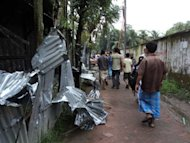 People walk past the ransacked homes of Buddhists in Ramu. Buddhists, who make up less than one percent of Bangladesh's 153 million population, are based mainly in southeastern districts, close to the border with Buddhist-majority Myanmar