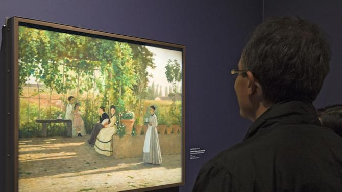 "A visitors looks at the painting ''After Lunch"" (La Pergola),1868, by Silvestro Lega, at the Orangerie Museum in Paris, Tuesday April 9, 2013. A new exhibit at Paris' Orangery museum called ""The Macchiaioli: the Italian Impressionists?"" explores how a Florence-based art movement that predated French impressionism by a decade was already using the themes of light, the outdoors and spontaneity that's more associated with the likes of Monet or Renoir. (AP Photo/Jacques Brinon)"