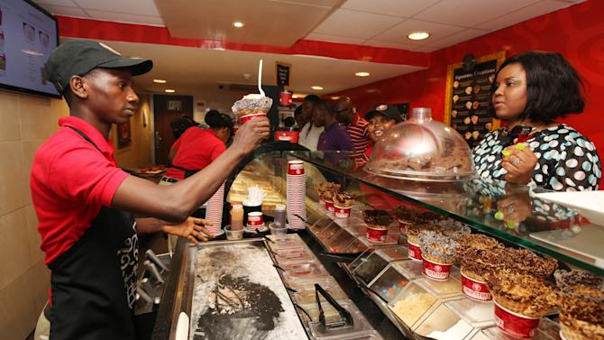 In this photo taken, Sunday, Feb. 10, 2013 customers buy Cold Stone ice cream in Lagos, Nigeria. As Nigeria's middle class grows along with the appetite for foreign brands in Africa's most populous nation, more foreign restaurants and lifestyle companies are entering the country. And the draw on Nigerians' new discretionary spending has also put new expectations on providing quality service in a nation where many have grown accustomed to expecting very little. ( AP Photo/Sunday Alamba)