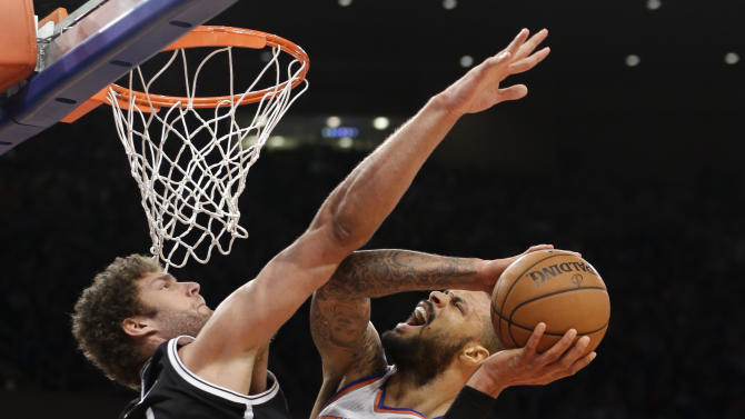 Brooklyn Nets center Brook Lopez (11) fouls New York Knicks center Tyson Chandler (6) in the first half of their NBA basketball game at Madison Square Garden in New York, Monday, Jan. 21, 2013. (AP Photo/Kathy Willens)