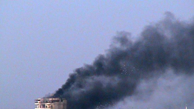 "In this March 9, 2012 citizen journalism image provided by the Homs City Union of The Syrian Revolution, smoke rise from a building that was shelled by the  Syrian army, at Jeb al-Jandali neighborhood in Homs province, central Syria. Two prominent Syrian dissidents said Wednesday they have quit the main opposition group that emerged from the year-old uprising against the regime in Damascus in protest over what one of the men described as an ""autocratic"" organization. (AP Photo/Homs City Union of The Syrian Revolution) THE ASSOCIATED PRESS IS UNABLE TO INDEPENDENTLY VERIFY THE AUTHENTICITY, CONTENT, LOCATION OR DATE OF THIS HANDOUT PHOTO"
