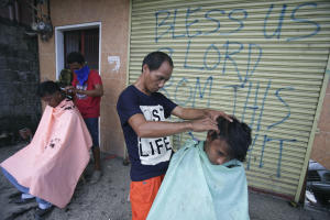 Typhoon survivors get a haircut along the streets for …