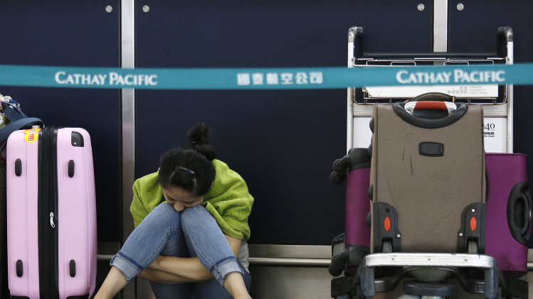 A passenger waits for flights to resume while sitting an airline counter at Hong Kong's international airport after Typhoon Usagi slammed into southern China, Monday, Sept. 23, 2013. The year's most powerful typhoon forced hundreds of flight cancellations, shut down shipping and train lines and killed nearly two dozen people. The typhoon wreaked havoc on airport schedules in HongKong, nearby Macau and mainland China, upsetting travel plans for many passengers who were returning home at the end of the three-day mid-autumn festival long weekend. (AP Photo/Vincent Yu)