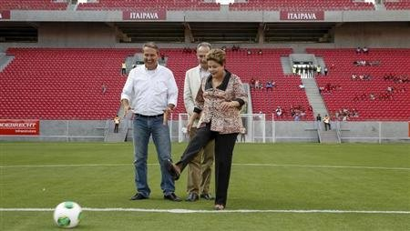 Brazil's President Dilma Rousseff kicks a soccer ball as she inaugurates the Arena Pernambuco stadium in Sao Lourenco da Mata
