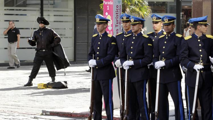 Uruguay's police officers line up to participate in a parade to commemorate the 184th anniversary of the Uruguayan police force, as a man dressed as The Zorro performs in the background, in Montevideo
