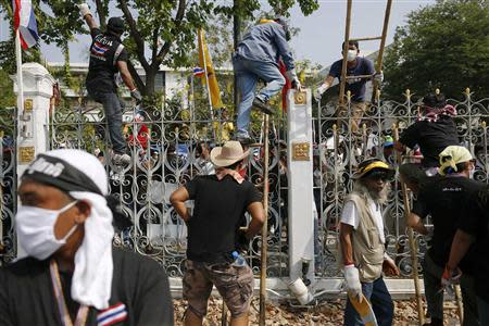 Anti-government protesters climb the fence to leave the compound of the Government house, after removing barbed wire installed by police, in Bangkok