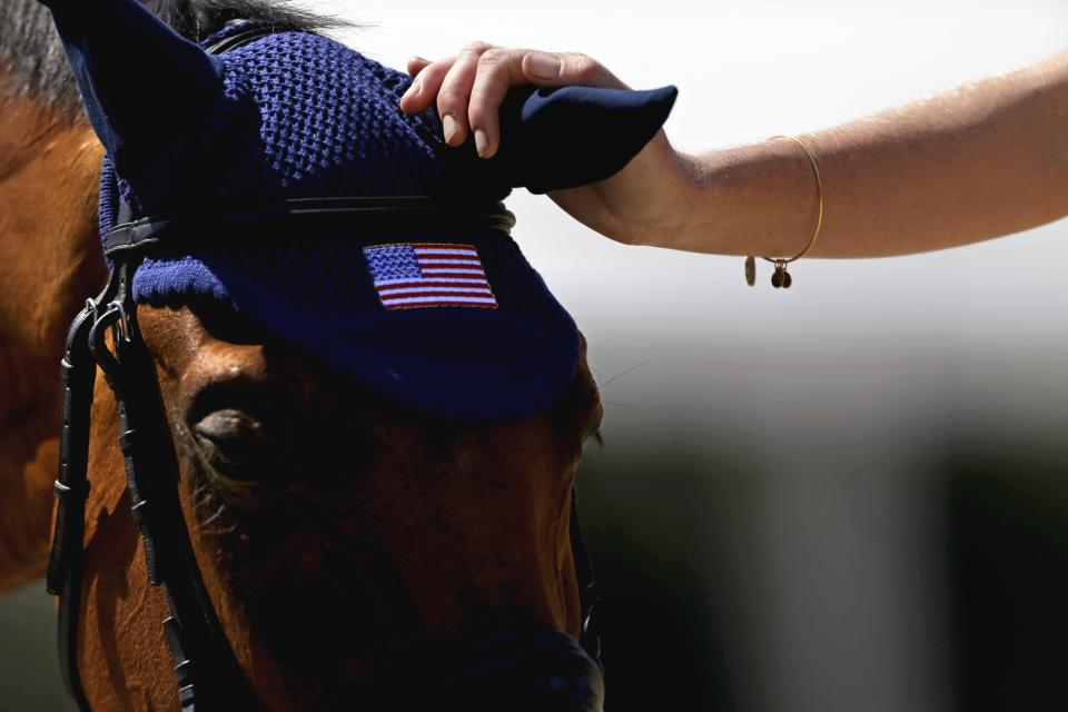 United States Equestrian team groom Sarah McKenna, right, pets Twizzle, after a training session with rider William Coleman for the equestrian eventing competition at the 2012 Summer Olympics, Thursday, July 26, 2012, in London. (AP Photo/David Goldman)