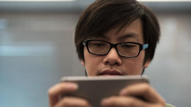 Mobile phone app designer Fung Kam-keung, CEO and founder of Awesapp Limited, plays one of his latest games, 'Yellow Umbrella', at the Awesapp Ltd. office in Hong Kong, on October 23, 2014