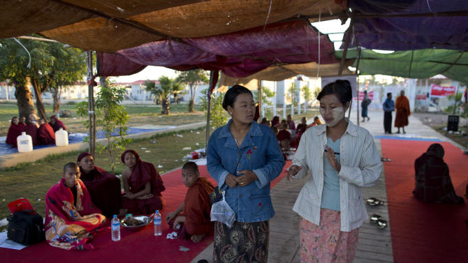 Activists Thwe Thwe Win, center left, and Aye Net, center right, walk through a make-shift tent where the protesting Buddhist monks occupy the office entrance to the Chinese copper mine company Wan Bao Co. Ltd in Letpadaung mine, Monywa township, northwestern Myanmar, Wednesday, Nov 28, 2012. Hundreds of Buddhist monks and villagers occupying a Letpadaung mine defied a government order to leave by Wednesday, saying they will stay until the project is halted. The protest is the latest example of increased activism by citizens since an elected government took over last year following almost five decades of repressive military rule. (AP Photo/Gemunu Amarasinghe)