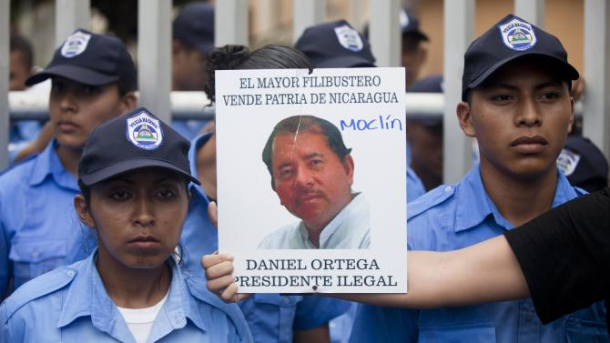 "A demonstrator holds out a picture of Nicaragua's President Daniel Ortega that reads in Spanish ""The biggest thief and traitor of Nicaragua, Daniel Ortega illegal President"" in front of a line of police during a protest against a canal project outside the National Assembly in Managua, Nicaragua, Thursday, June 13, 2013. A multi-billion dollar proposal to plow a massive rival to the Panama Canal across the middle of Nicaragua was approved by the National Assembly Thursday, capping a lightning-fast approval process that has provoked deep skepticism among shipping experts and concern among environmentalists. (AP Photo/Esteban Felix)"