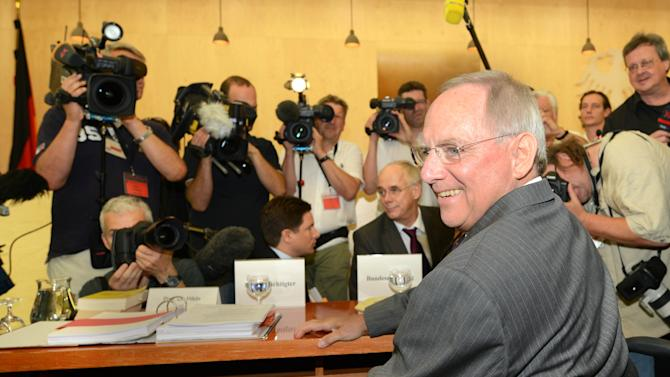 German Finance Minister Wolfgang Schaeuble is surrounded by journalists at the German Constitutional Court in Karlsruhe, southern Germany, Tuesday July 10, 2012. Germany's highest court is to hear arguments Tuesday against the country signing up to the Europe's emergency bailout fund and a new treaty limiting debt. Opponents of the treaties argue that joining the bailout fund and debt pact for the 17 countries that use the euro would impose limits on the German Parliament's constitutional power to say how taxpayer money is spent. (AP Photo/dapd/Ronald Wittek)