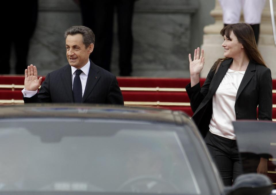 Outgoing French President Nicolas Sarkozy and his wife Carla Bruni-Sarkozy leave the Elysee Palace after the handover ceremony with new President Francois Hollande, Tuesday, May 15, 2012 in Paris.  (AP Photo/Michel Euler)