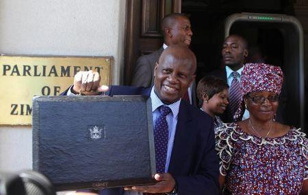 Zimbabwe's Finance Minister Chinamasa arrives with his wife Monica to deliver the 2015 national budget to the parliament in Harare