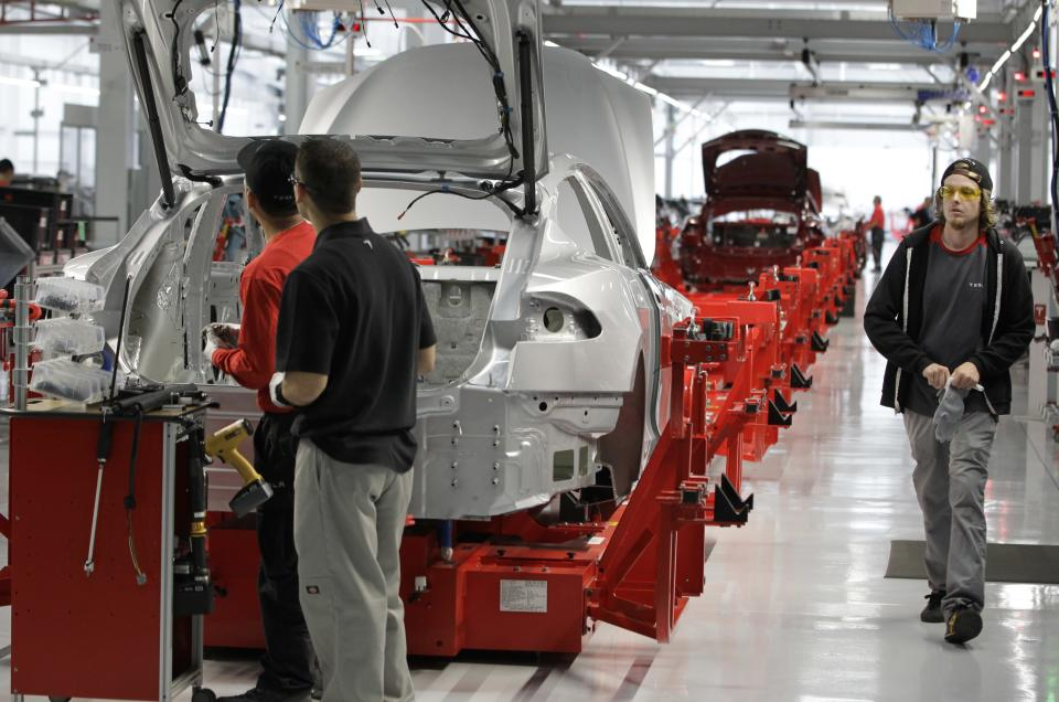 Assembly workers put together a Tesla Model S at the Tesla factory in Fremont, Calif., Friday, June 22, 2012. The first Model S sedan car will be rolling off the assembly line on Friday.  (AP Photo/Paul Sakuma)