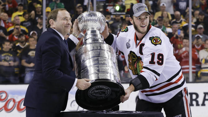 NHL Commissioner Gary Bettman, left, and Chicago Blackhawks captain Jonathan Toews pose with the Stanley Cup after the Blackhawks beat the Boston Bruins 3-2 in Game 6 of the NHL hockey Stanley Cup Finals Monday, June 24, 2013, in Boston. (AP Photo/Elise Amendola)