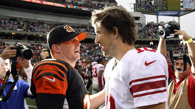 Cincinnati Bengals quarterback Andy Dalton (14) meets with New York Giants quarterback Eli Manning (10) after the Bengals' 31-13 win in an NFL football game, Sunday, Nov. 11, 2012, in Cincinnati. (AP Photo/Tom Uhlman)