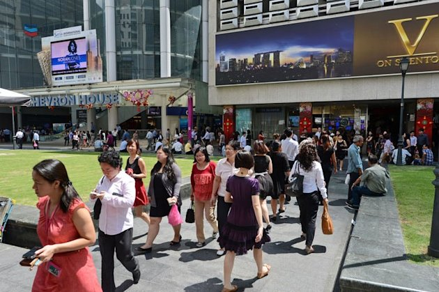 Pedestrians walk down a street in downtown financial district in Singapore on January 29, 2013. Singapore&#39;s population may reach almost seven million by 2030, up from 5.31 million currently, with the number of citizens shrinking to barely half of the total, the government said