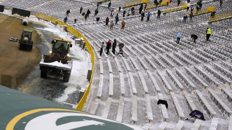 Shovelers clear snow between bleachers at Lambeau Field in Green Bay, Wisconsin