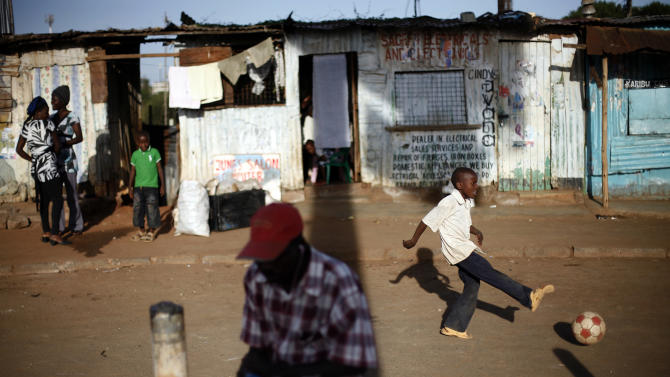 Kenyans gather outside as a child plays as preliminary results trickle in for Monday's general election, in the Kibera slum of Nairobi, Kenya, Tuesday, March 5, 2013. Kenya on Monday held its first presidential election since the 2007 vote which ushered in months of tribal violence that killed more than 1,000 people and displaced 600,000 from their homes. Some shopkeepers closed their shops fearing a repeat of 2007 violence. (AP Photo/Jerome Delay)