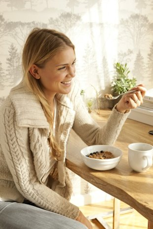 Woman eating cereal and coffee for breakfast