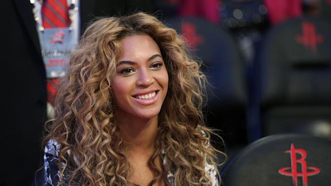 FILE - In a Sunday, Feb. 17, 2013 file photo, Beyonce sits courtside before the NBA All-Star basketball game, in Houston. Red-carpet arrivals of celebrities such as Beyonce and Rooney Mara at The Metropolitan Museum of Art's Costume Institute Benefit on May 6, 2013 will be streamed live on Vogue.com. Beyonce is billed as the event's honorary chairwoman, with co-chairs Mara, Givenchy creative director Riccardo Tisci, Vogue editor-in-chief Anna Wintour and Lauren Santo Domingo, co-founder of online retailer Moda Operandi. (AP Photo/Eric Gay, File)