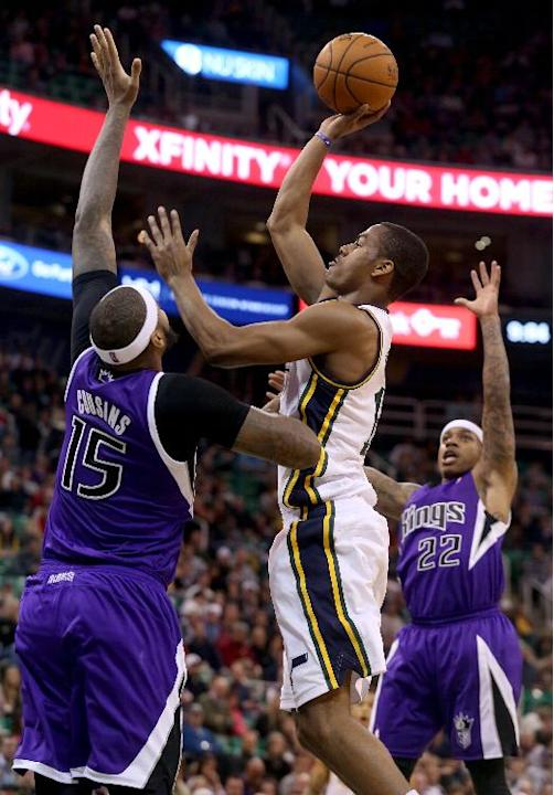 Sacramento Kings' DeMarcus Cousins (15) and Sacramento Kings' Isaiah Thomas (22) defend as Utah Jazz's Alec Burks, center, takes a shot in the second half of an NBA basketball game on Satu