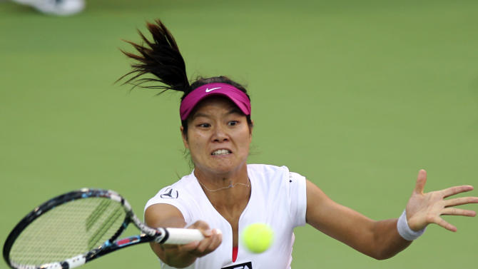Na Li of China returns the ball to Magdalena Rybarikova of Slovakia during the third day of the WTA Qatar Ladies Open in Doha, Qatar,Wednesday, Feb. 12, 2014. (AP Photo/Osama Faisal)