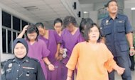 Enam tersangka wanita saat dibawa keluar dari Mahkamah Majistret Bukit Mertajam, setelah ditahan semalam.