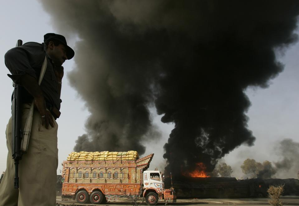 Pakistani police officer stands guard on still smoldering oil trucks in Shikarpur, southern Pakistan on Friday Oct. 1, 2010. Suspected militants set ablaze at least 27 tankers carrying fuel for U.S. and NATO troops in Afghanistan on Friday, police said. (AP Photo/Aaron Favila)