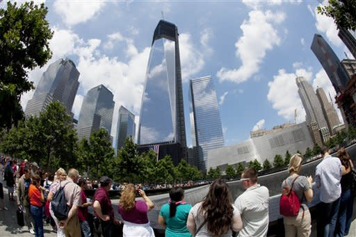 Visitors to the National September 11 Memorial get a view of One World Trade Center, center, Thursday, June 14, 2012 in New York. President Barack Obama is scheduled to visit the site later Thursday. (AP Photo/Mark Lennihan)