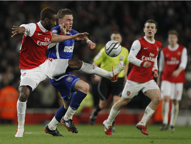 Arsenal's Johan Djourou, left, competes for the ball with Ipswich Town's Connor Wickham during the English League Cup semifinal soccer match between Arsenal and Ipswich Town at the Emirates stadium in