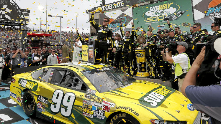 Carl Edwards celebrates winning the NASCAR Sprint Cup Series auto race, Sunday, March 3, 2013, in Avondale, Ariz. (AP Photo/Matt York)