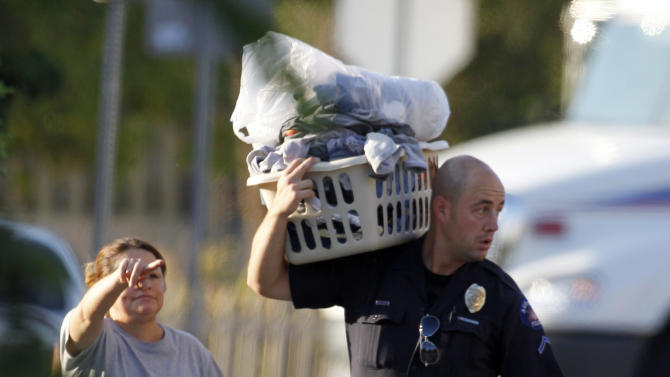"""Alma Cardona, left, directs an Aurora police officer carrying some of her items, after she was allowed in to get some belongings from her home near the apartment of alleged gunman James Holmes Friday, July 20, 2012 in Aurora, Colo. Authorities report that 12 died and more than three dozen people were shot during an assault at the theatre during a midnight premiere of """"The Dark Knight."""" Colorado firefighters are monitoring the Aurora apartment building for gases in an effort to determine what chemicals they say 24-year-old James Holmes might have used to trap the place _ in case the materials go off.  (AP Photo/Alex Brandon)"""