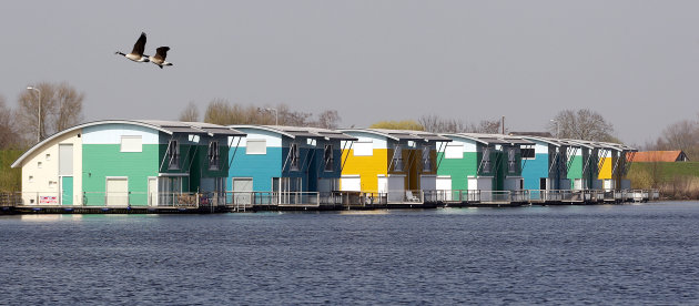 In this photo taken Wednesday, March 28, 2012 birds fly above floating homes on the River Maas in Maasbommel, Netherlands. The Netherlands, a third of which lies below sea level, has been managing wat