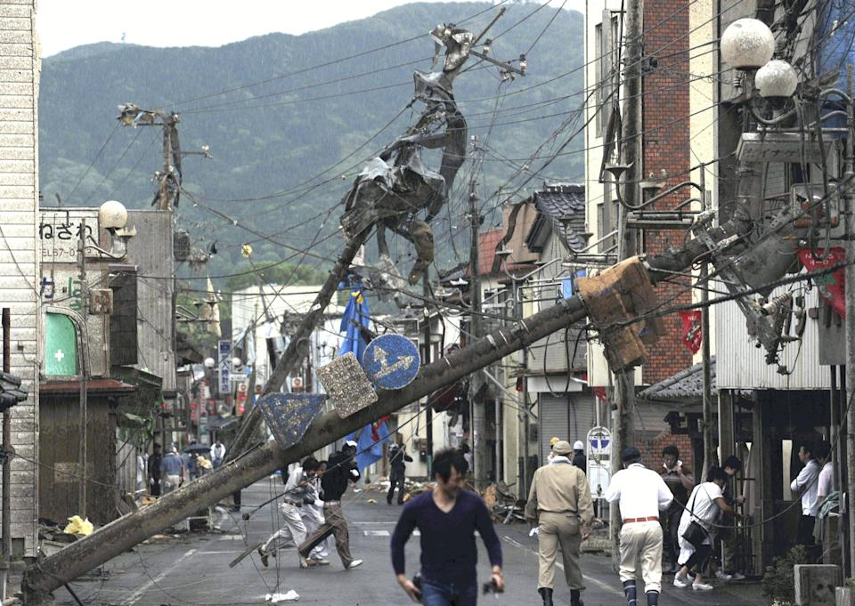 Residents walk under fallen power poles after a tornado struck Tsukuba city, northeast of Tokyo, Sunday, May 6, 2012. The tornado tore through the area, injuring at least 30 people, destroying dozens of homes and leaving thousands more without electricity. (AP Photo/Yomiuri Shimbun, Tetsu Joko) JAPAN OUT