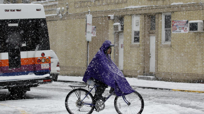 A person rides a bicycle as snow falls over the Northern New Jersey region during a rare October snowstorm, Saturday, Oct. 29, 2011, in North Bergen, N.J.   (AP Photo/Julio Cortez)