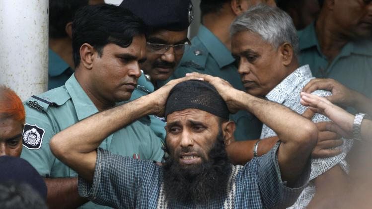 A prisoner reacts as police force him into a van after the verdict for a 2009 mutiny is announced, in Dhaka