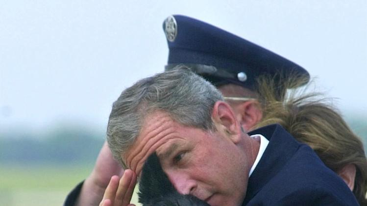 FILE - In this June 25, 2001 file photo, President Bush does his best to salute while holding his dog Barney as they get off of Air Force One at Andrews Air Force Base, Md. Barney, former White House Scottish Terrier and star of holiday videos shot during President George W. Bush's administration, has died after suffering from cancer. He was 12.  (AP Photo/Susan Walsh, File)