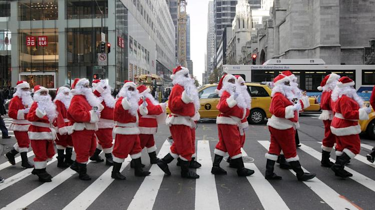 Volunteers of America Santas ring their bells as the cross a street in Fifth Ave. during their 110th annual Sidewalk Santa Parade, in New York,  Friday, Nov. 23, 2012. The donations they raise are used for a holiday food voucher program for needy residents. (AP Photo/Richard Drew)