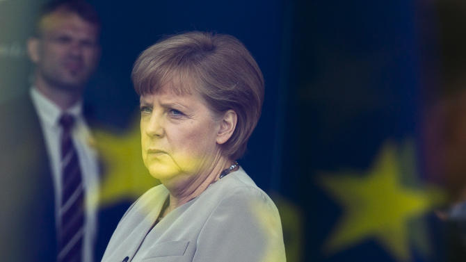 FILE - The June 12, 2012 file photo shows German Chancellor Angela Merkel behind a window with a reflection of the European flag at the chancellery in Berlin, Germany. By rejecting an EU bailout and turning to Russia for help, Cyprus is exposing growing frustration and dwindling solidarity within a bloc that was meant to bring the continent closer together after World War II. The chaos over the rescue plan, which the Cypriot parliament roundly rejected Tuesday, has renewed many of doubts about the legitimacy of the European project _ notably over perceived German dominance and threats to national sovereignty. The extraordinary spectacle of an EU member seeking salvation from the old Cold War enemy has raised deep questions about how far Europe can and will go to take care of its own. (AP Photo/Markus Schreiber)