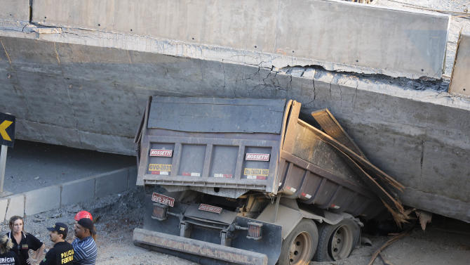A truck is trapped underneath a collapsed bridge in Belo Horizonte, Brazil, Thursday, July 3, 2014. The overpass under construction collapsed Thursday in the Brazilian World Cup host city. The incident took place on a main avenue, the expansion of which was part of the World Cup infrastructure plan but, like most urban mobility projects related to the Cup, was not finished on time for the event